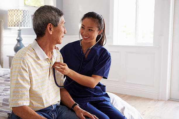 Nurse Making Home Visit To Senior Man For Medical Exam stock photo