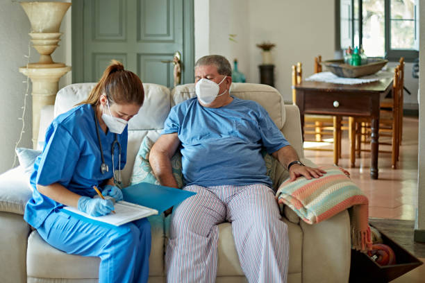 Nurse Making House Call to Care for Senior Man in Recovery stock photo