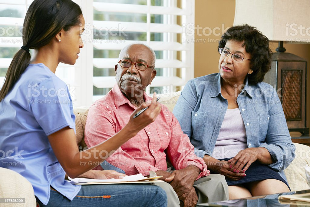Nurse Making Notes During Home Visit With Senior Couple stock photo