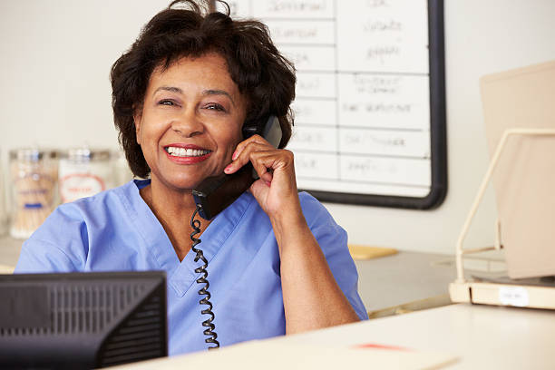 nurse making phone call at nurses station - nurse on phone stock photos and pictures