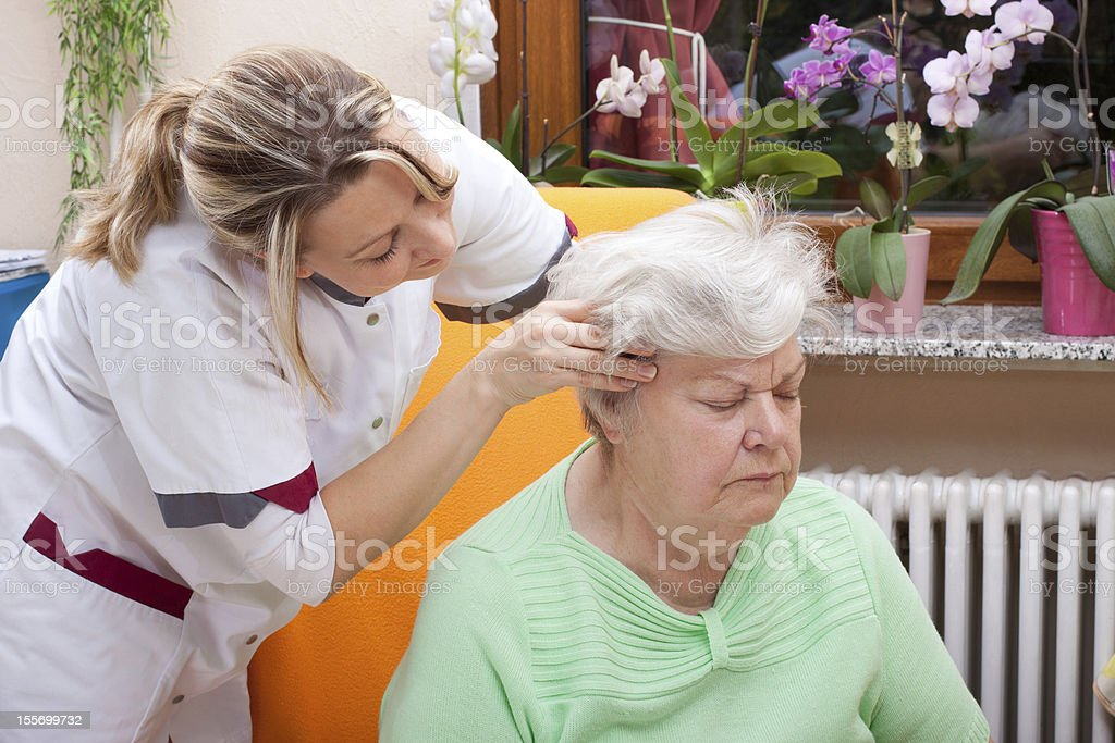 Nurse massages the head of a senior royalty-free stock photo