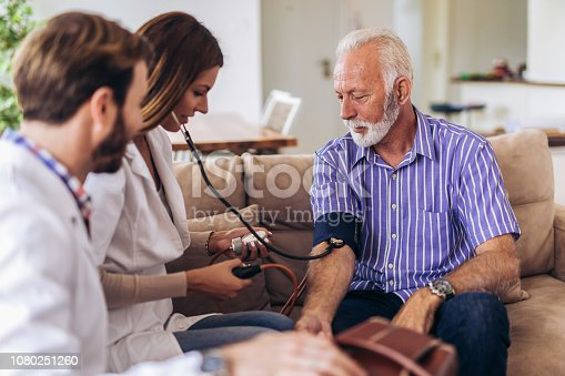 istock Nurse measuring blood pressure of senior man at home. Smiling to each other. Home care. 1080251260