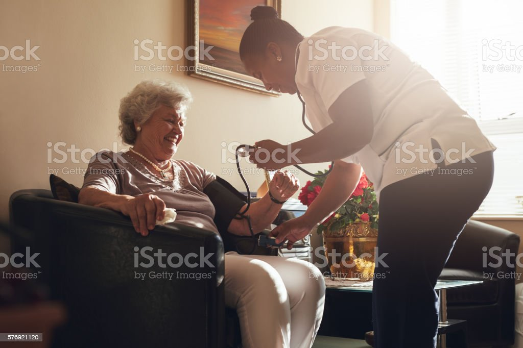 Nurse measuring blood pressure of senior woman patient in retirement...