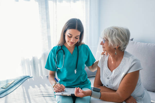 nurse measuring blood pressure of senior woman at home - nurse stock pictures, royalty-free photos & images
