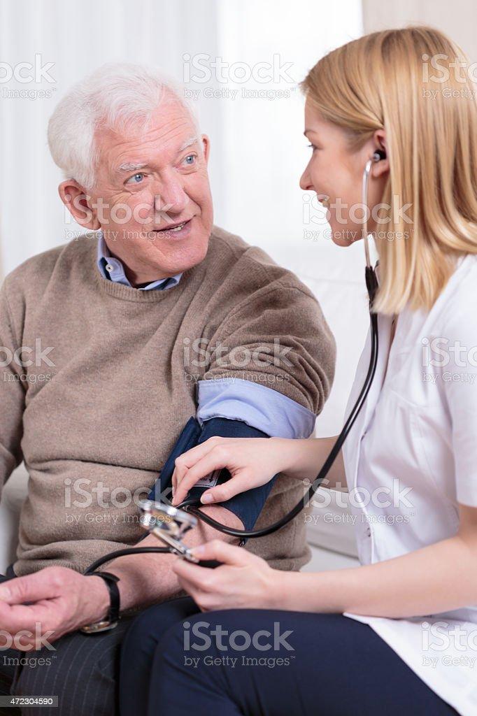 Nurse measuring blood pressure stock photo