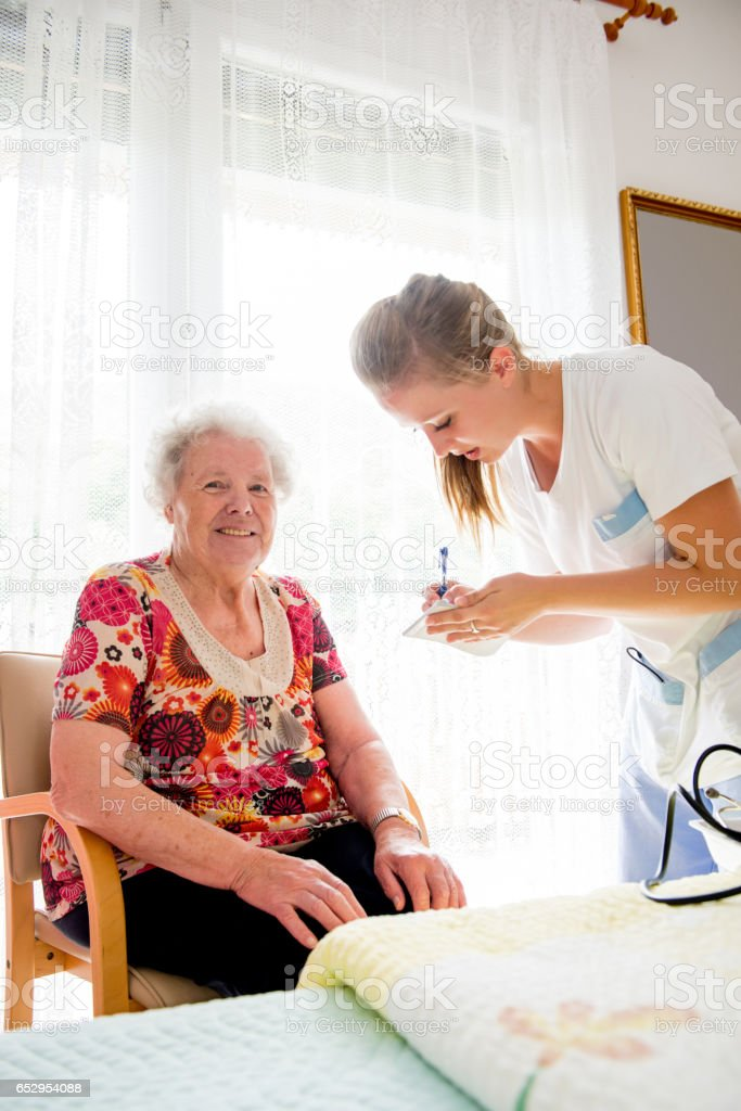 Nurse Measuring Blood Pressure To A Senior Woman In The Nursery Home