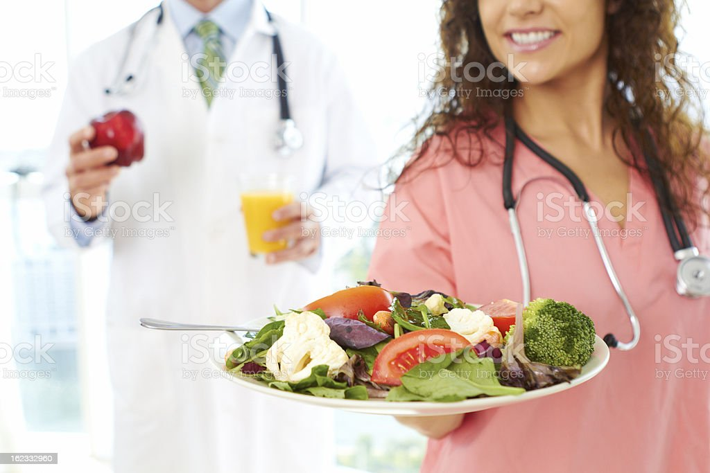 Nurse offering a plate of healthy food as medicine royalty-free stock photo