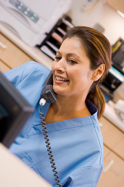 nurse on the telephone at reception area - nurse on phone stock photos and pictures