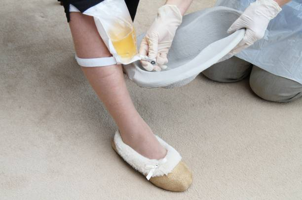 Nurse or care worker emptying urine drainage bag stock photo