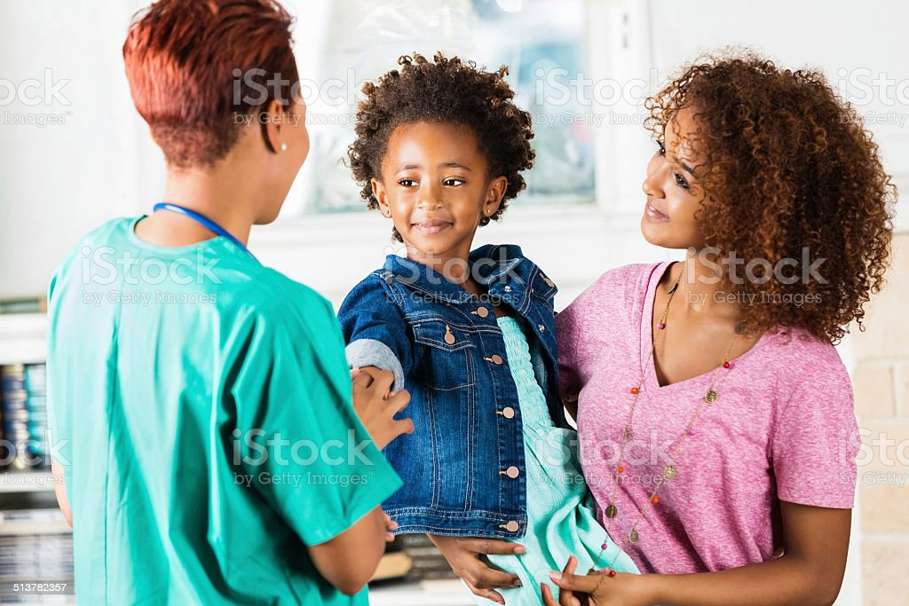 Nurse or doctor checking on young patient during healthcare appointment stock photo