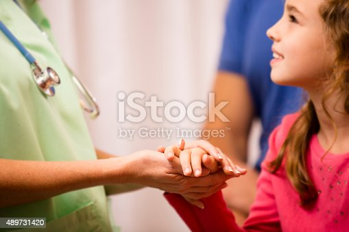 istock Nurse or doctor consoles, holds hand of child patient. 489731420