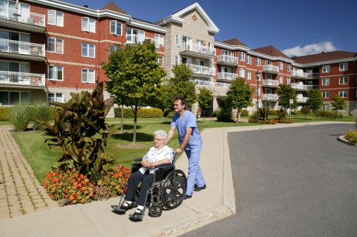 nurse or doctor pushing a wheelchair outdoors