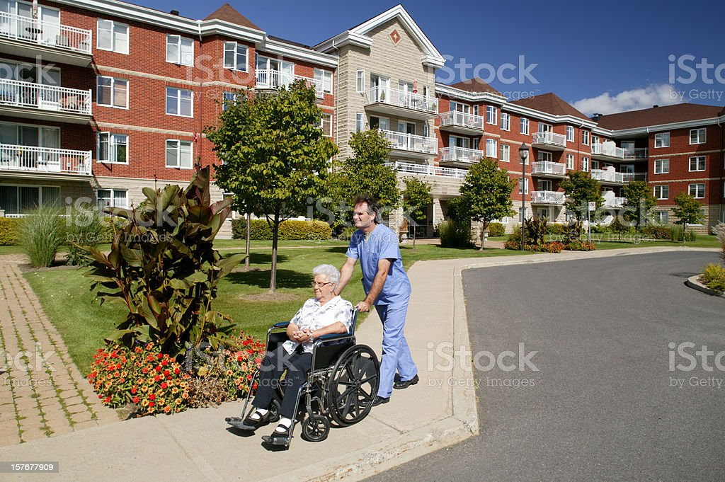 nurse or doctor pushing a wheelchair outdoors stock photo
