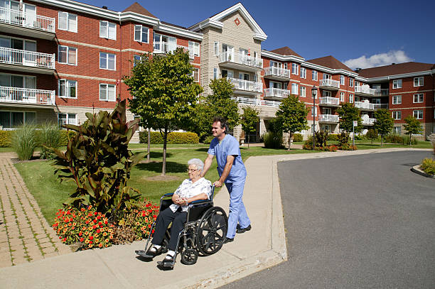 nurse or doctor pushing a wheelchair outdoors - ouderenzorg stockfoto's en -beelden