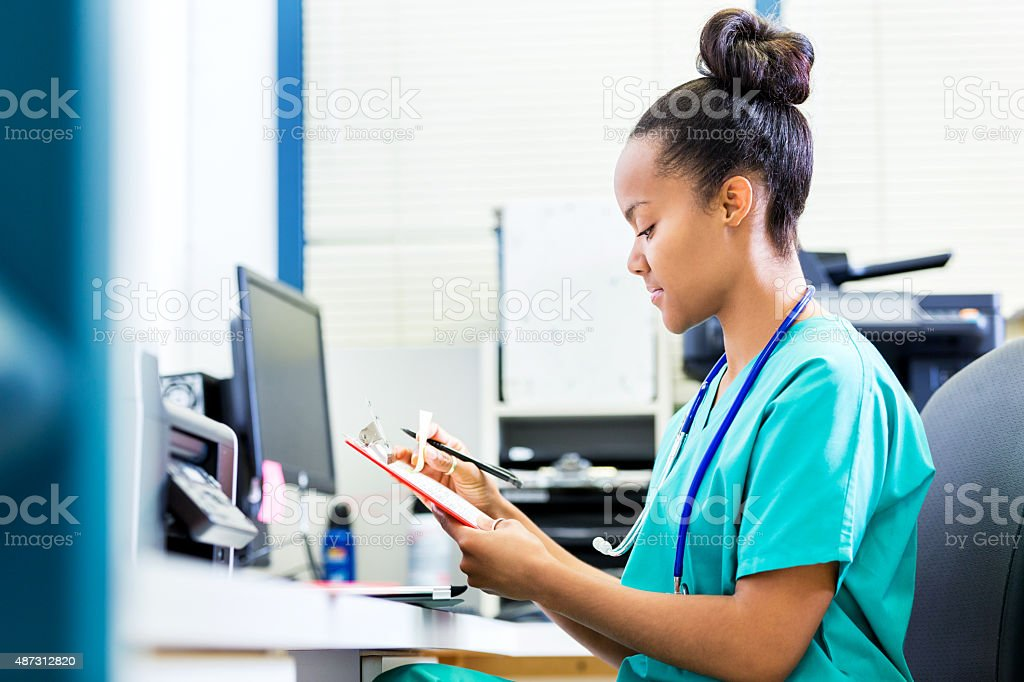 Enfermeira ou o médico atualizando paciente no hospital estação de enfermagem gráficos - foto de acervo