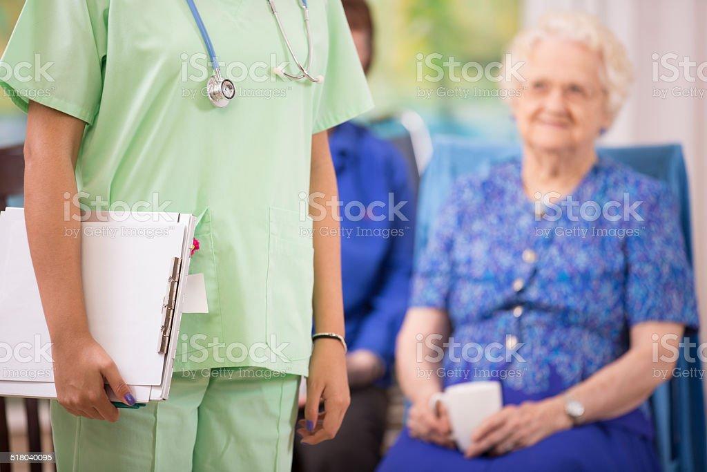 Female doctor or nurse visits elderly patients in a nursing home or...