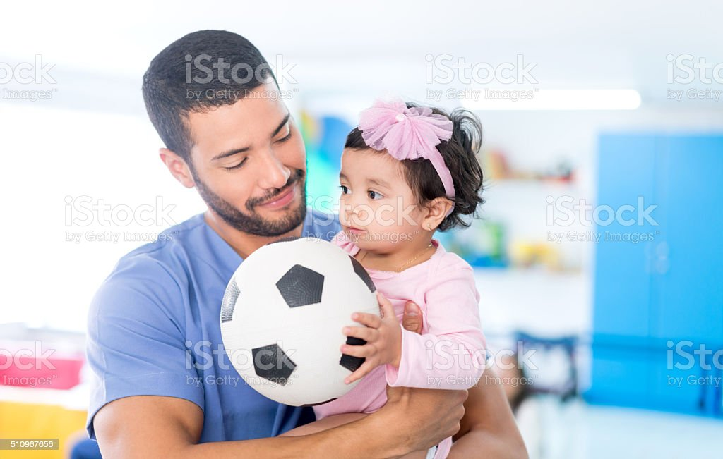 Nurse playing football with a little girl - foto de stock