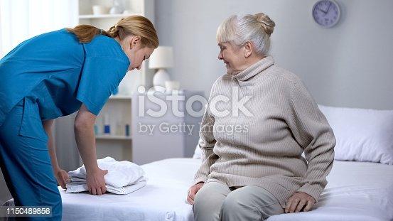Nurse preparing clean bed-linen to elderly female patient in medical center