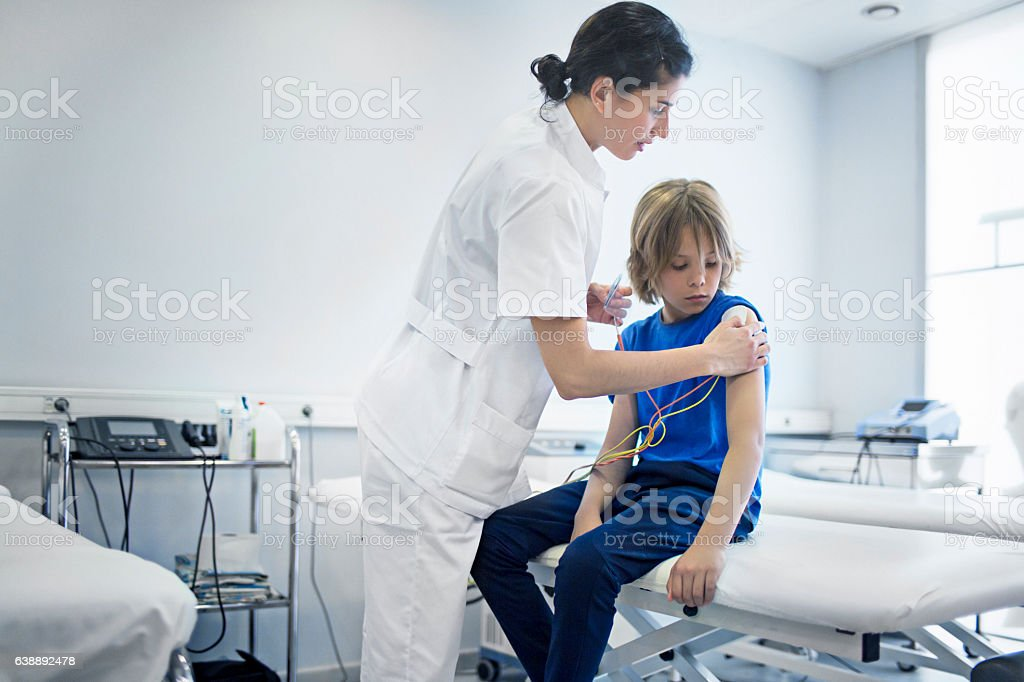 Nurse preparing for TENS therapy on boy in clinic stock photo