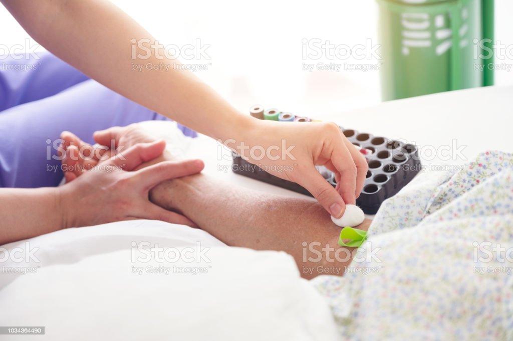 Krankenschwester Vorbereitung Patient eine Blutanalyse mit Adern Betrachter Gerät zu tun. Krankenschwester desinfizierende Patient Arm von Wattestäbchen. Tampon in der Hand des Patienten Impfung Konzept – Foto