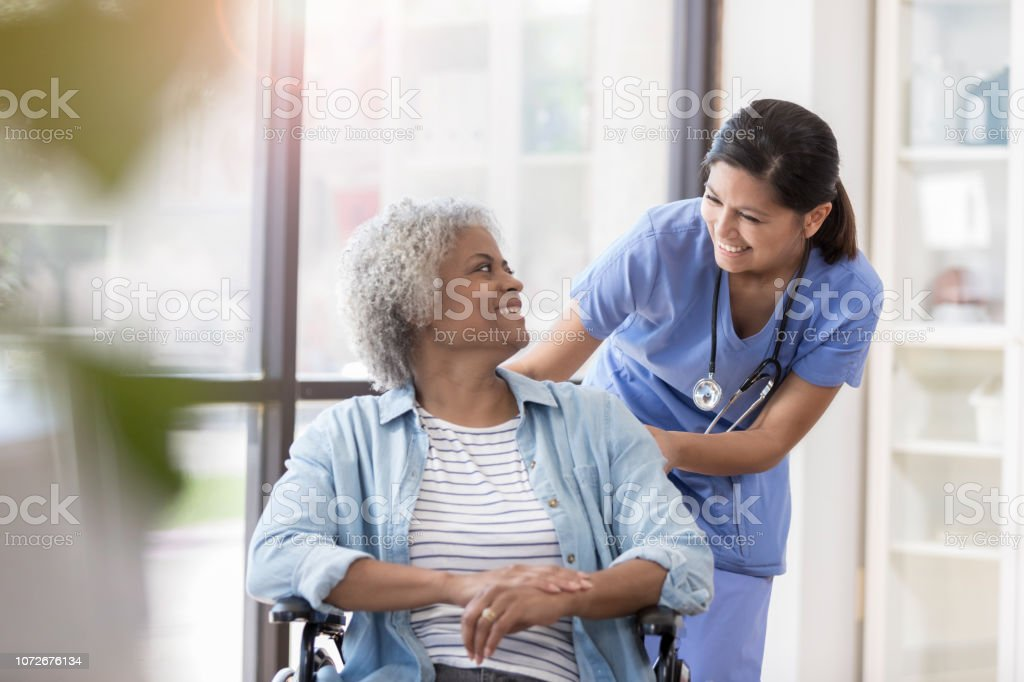 Nurse pushes female patient in wheelchair stock photo
