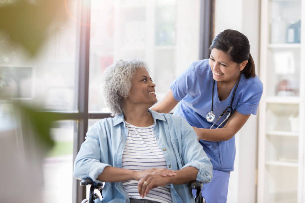 nurse pushes female patient in wheelchair - elderly patients stock photos and pictures