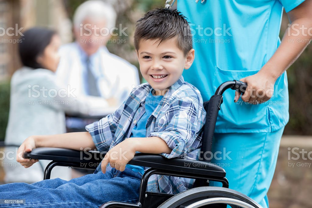 Nurse pushes happy young male patient in wheelchair stock photo
