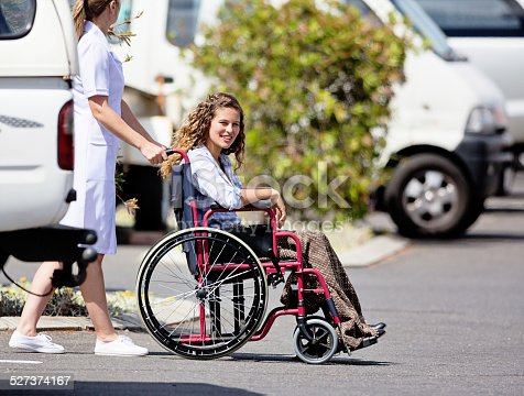 istock Nurse pushes smiling young woman in wheelchair past hospital ambulances 527374167
