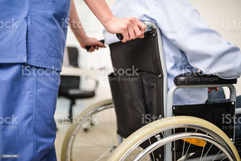 Nurse pushing a wheelchair stock photo
