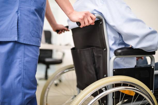 Nurse pushing a wheelchair stock photo