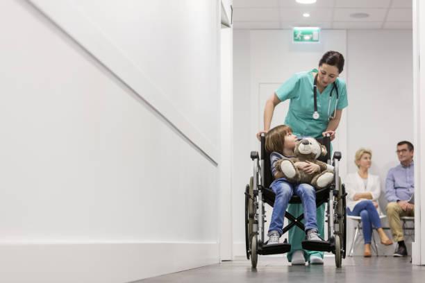 Krankenschwester schiebt Jungen mit Teddybär auf den Rollstuhl, während Patienten im Krankenhauskorridor warten – Foto