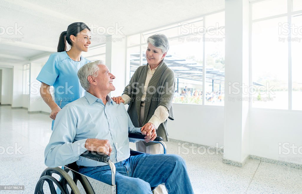 "Nurse pushing senior male in a wheelchair at the hospital Happy nurse pushing senior male in a wheelchair at the hospital and talking to his wife -€"" healthcare and medicine Accessibility Stock Photo"