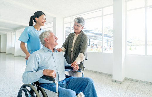 Nurse Pushing Senior Male In A Wheelchair At The Hospital Stock Photo - Download Image Now