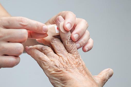 909806032 istock photo Nurse putting adhesive bandage on elderly woman hand 687112380