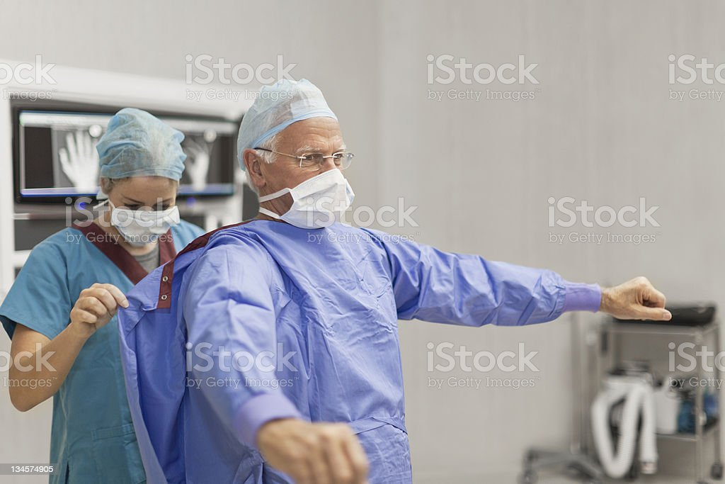 Nurse putting coat on surgeon stock photo