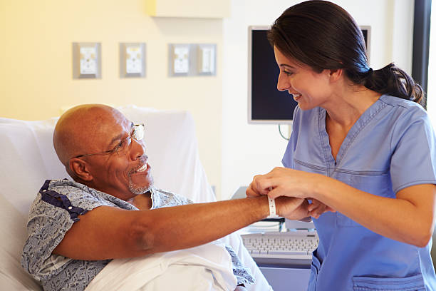 Nurse Putting Wristband On Senior Male Patient In Hospital Happy Smiling Nurse Putting Wristband On Senior Male Patient In Hospital wristband stock pictures, royalty-free photos & images