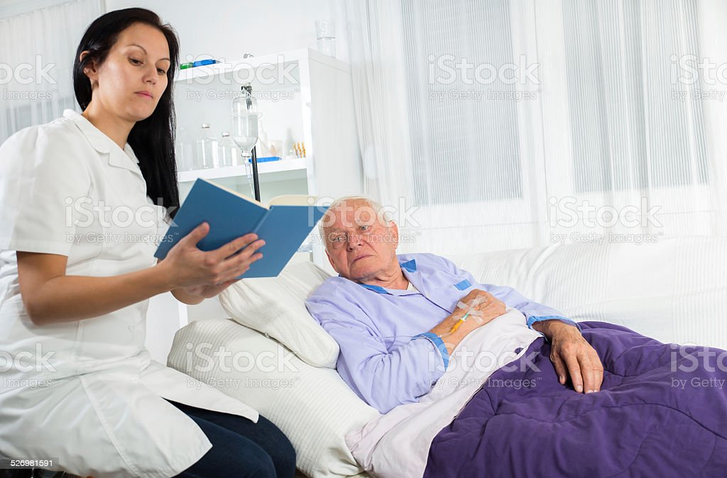 Nurse reading a book to his patient stock photo