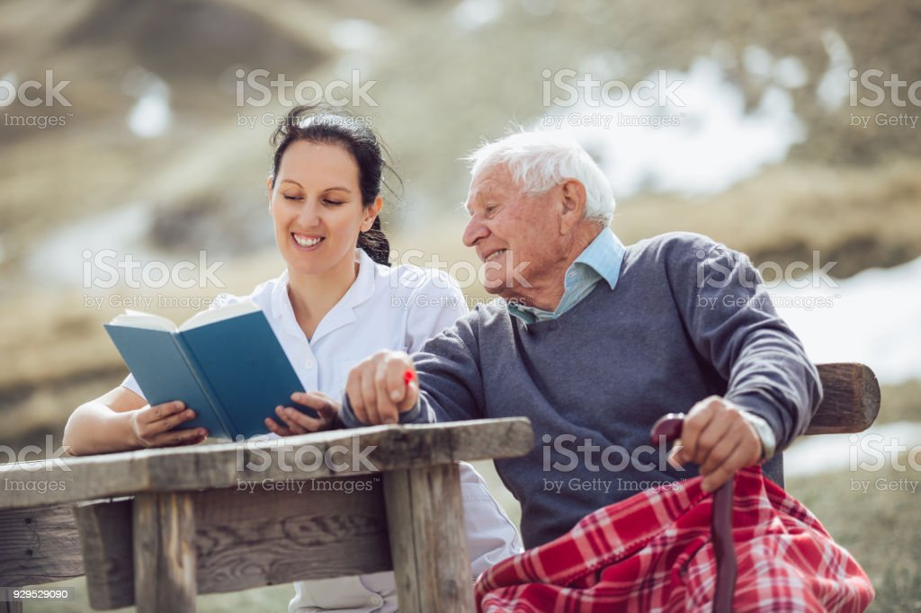 Libro de lectura de enfermera para hombre senior - foto de stock