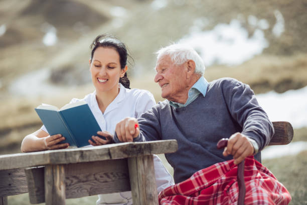 krankenschwester-lesebuch, senior woman - hospiz stock-fotos und bilder