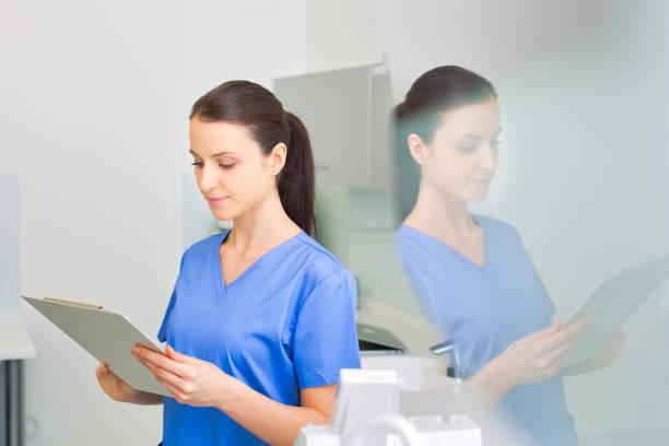 Enfermera revisando el informe médico en el portapapeles en la clínica dental - foto de stock