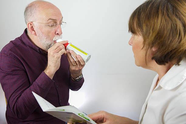 Infermiere recensioni capacità polmonare del paziente con misuratore del picco di flusso espiratorio - foto stock
