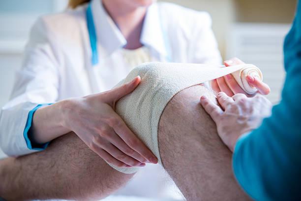 nurse rewinding knee bandage - knäskål bildbanksfoton och bilder
