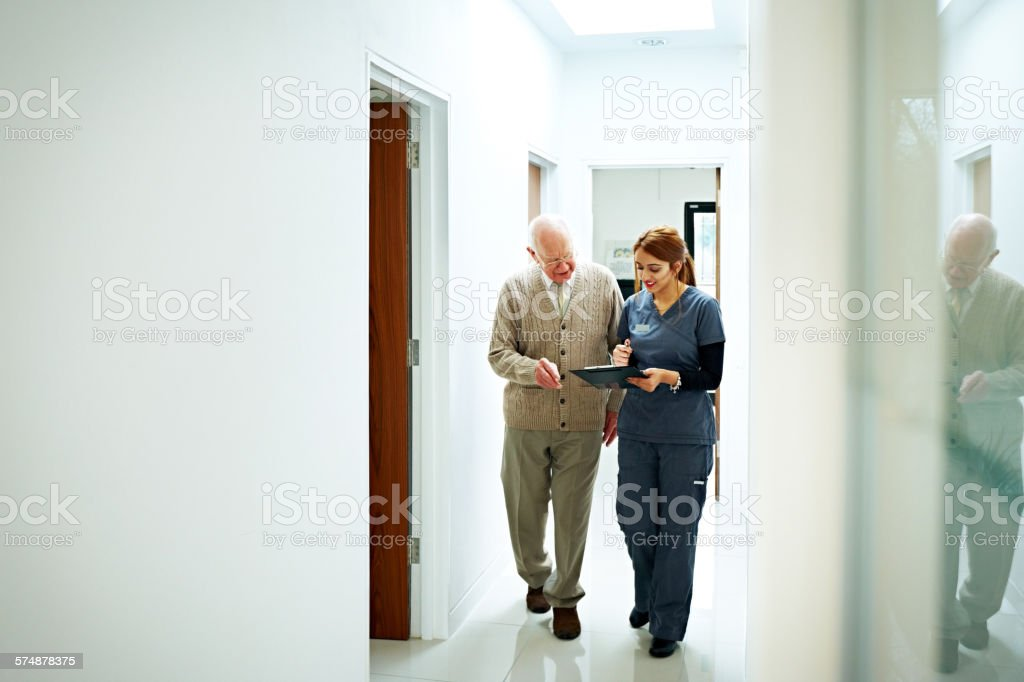 Nurse sharing medical report with senior patient - foto de stock