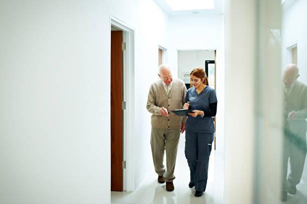 nurse sharing medical report with senior patient - two dentists talking bildbanksfoton och bilder