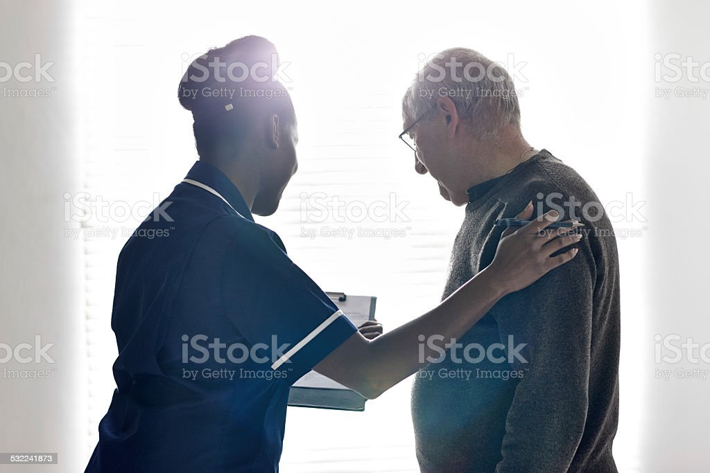 Nurse showing medical report to senior patient at hospital stock photo