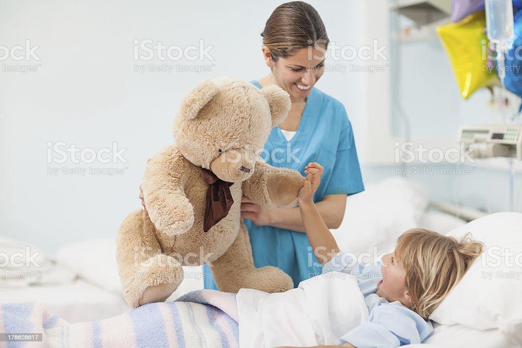 Nurse showing teddy bear to child stock photo