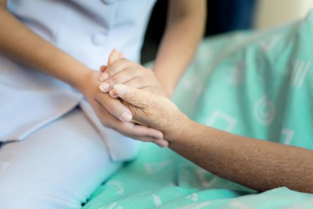 Krankenschwester, sitzt auf einem Krankenhausbett neben einer älteren Frau, helfende Hände, Pflege für das ältere Konzept – Foto