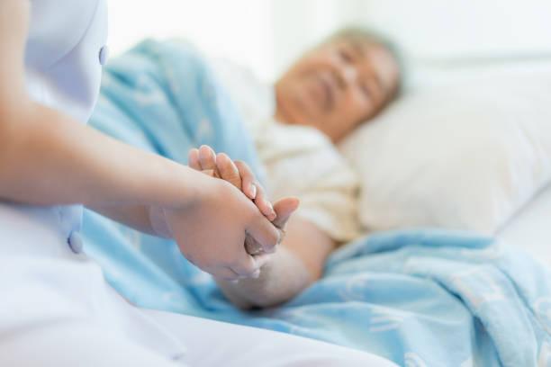 enfermera sentada en una cama de hospital al lado de una mujer mayor, ayudando a las manos, cuidar el concepto tercera edad - geriatría fotografías e imágenes de stock