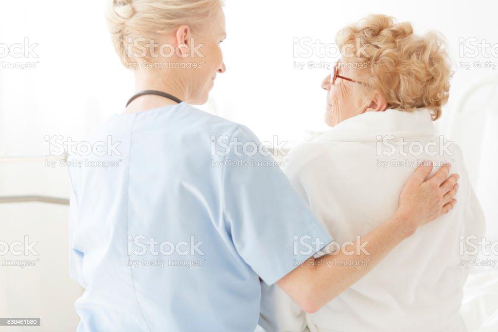 Enfermera, sentado en una cama de hospital - foto de stock