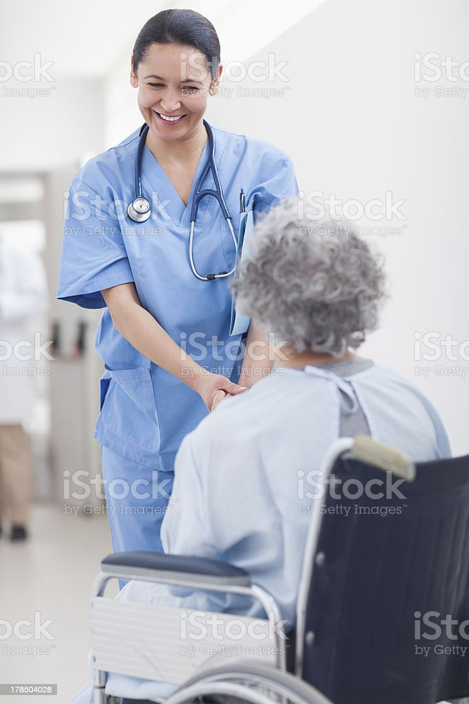 Nurse smiling while holding the hands of a patient royalty-free stock photo